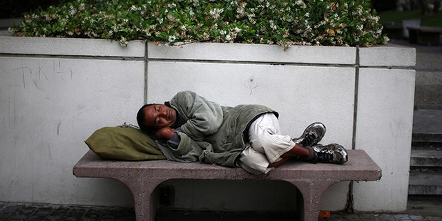 A man sleeps on a bench in downtown Los Angeles, California, May 31, 2017