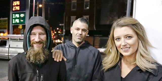 When Kate McClure, right, ran out of gas, Johnny Bobbitt Jr., left, who is homeless, gave his last $20 to buy gas for her. McClure, seen with boyfriend Mark D'Amico, middle, started a Gofundme.com campaign for Bobbitt that has raised more than $13,000. (Elizabeth Robertson/The Philadelphia Inquirer via AP)