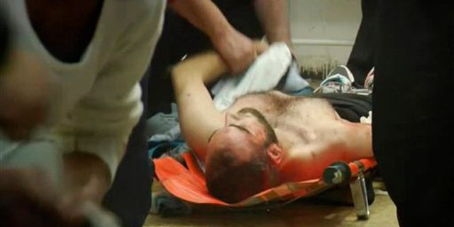 This image taken from video filmed over the past several days by an independent cameraman and made available Feb. 7, 2012, shows medical staff trying to help the injured at a hospital in Homs, Syria.