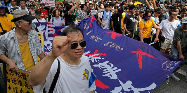 """Protesters carry a banner with Chinese words """"End the one party rule in China"""" as thousands of protesters march along a downtown street during an annual pro-democracy protest in Hong Kong Sunday, July 1, 2018."""