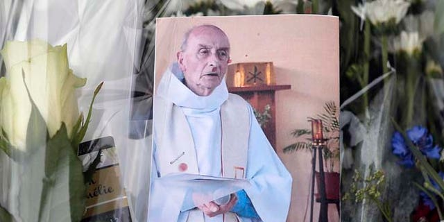 A picture of late Father Jacques Hamel is placed on flowers at the makeshift memorial