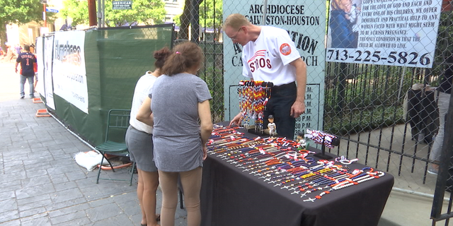 Volunteers from the Church of the Annunciation sell Astros-themed rosary beads two hours before home games.