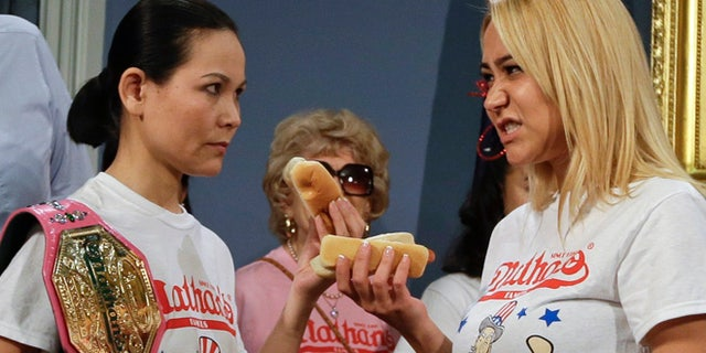 July 3, 2014: New York City Mayor Bill de Blasio watches hot dog eating contestants Sonya Thomas, left, and Miki Sudo, right, during a news conference to promote the upcoming Nathan's Famous Fourth of July Hot Dog Eating Contest.