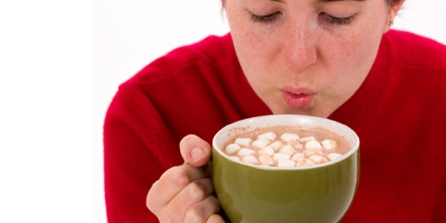 Close-up of a woman trying to cool a hot cup of cocoa by blowing on it.