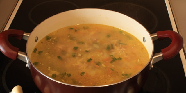 Fresh delicious pot of soup on the stove and garlic