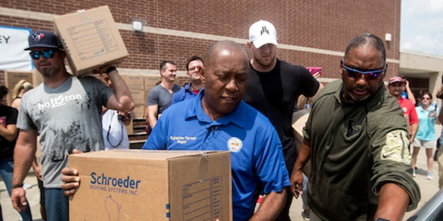 Houston Mayor Sylvester Turner, center, with Houston Texans Shane Lechler, left, and J.J. Watt, second right, distribute relief supplies to people impacted by Hurricane Harvey on Sunday, Sept. 3, 2017, in Houston. Watt's Hurricane Harvey Relief Fund has raised millions of dollars to help those affected by the storm. (Brett Coomer/Houston Chronicle via AP, Pool)