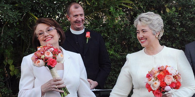 In this photo provided by the Houston mayor's office, Houston Mayor Annise Parker, right and her long-time partner, First Lady Kathy Hubbard, celebrate at their wedding Thursday, Jan 16, 1014 in Palm Springs, Calif. The ceremony was performed by the Rev. Paul Fromberg, rear, rector of St. Gregory of Nyssa Episcopal Church in San Francisco. (AP/Houston Office of The Mayor, Richard Hartog)