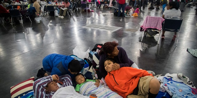 Oscar Galindo, Donato Galindo, 2, Oscar Galindo, 11, Andre Galindo, 9, and Maria Rodriguez relax while taking shelter at the George R Brown Convention Center on Monday, Aug. 28, 2017, in Houston.