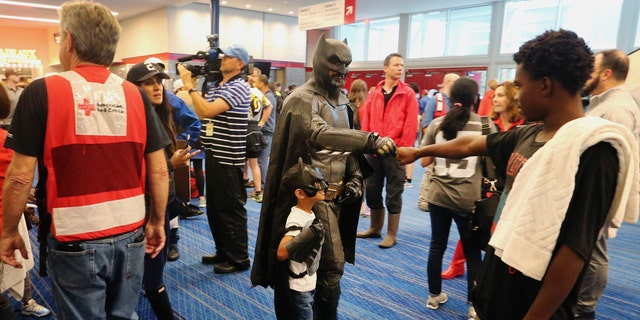 A man dressed as Batman shakes hands with people as they arrive at the Red Cross shelter at the George Brown Convention Center in Houston, Monday, Aug. 28, 2017, in the wake of Tropical Storm Harvey.