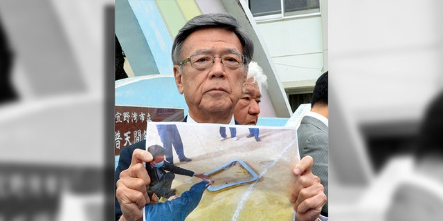 Okinawa Gov. Takeshi Onaga holding a picture of the fallen metal window frame.