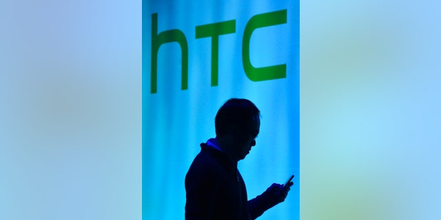 File photo - A man uses his mobile phone during the launch of the HTC One smartphone in London Feb. 19, 2013. (REUTERS/Toby Melville)