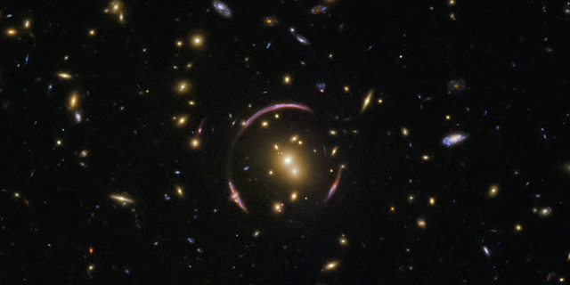 """The graceful arcs at the center of this image from the Hubble Space Telescope are actually the distorted light of distant galaxies, twisted to form an """"Einstein ring"""" by the gravitational influence of the closer galaxy cluster SDSS J0146-0929."""