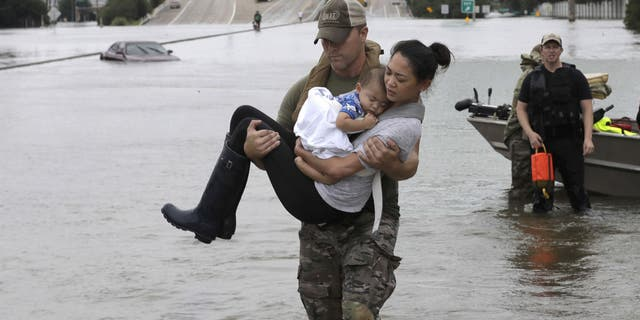 In an image that went viral online, Houston Police SWAT Officer Daryl Hudeck carried a Houston mom and her sleeping baby through knee-deep floodwaters in southwest Houston.