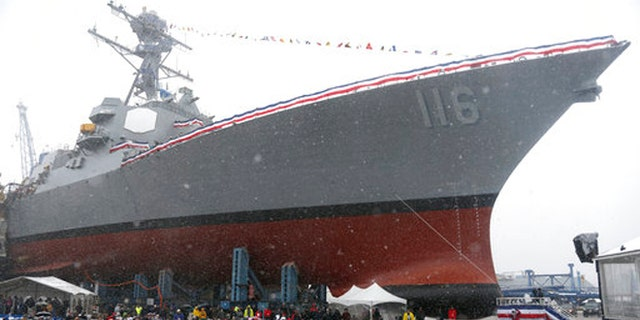 The future USS Thomas Hudner, a U.S. Navy destroyer named after Korean War veteran Thomas Hudner, looms over the audience during a christening ceremony at Bath Iron Works in Bath, Maine, Saturday.
