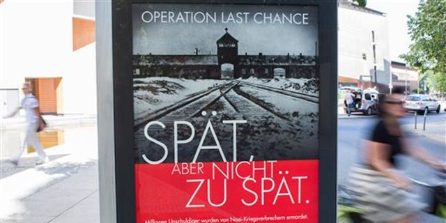 """July 23: A placard reading """"Operation last chance - late but not too late"""" is displayed in Berlin, Germany. With 2,000 placards in Berlin, Hamburg and Cologne cities the Simon Wiesenthal Center launched another campaign to find and prosecute Nazi war criminals while they are still alive."""