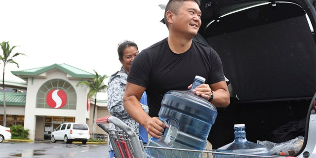 Hawaii residents seen loading water into their car ahead of the impending storm.