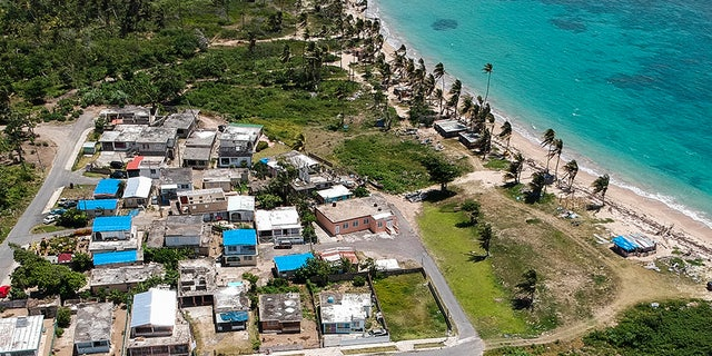 This June 18, 2018 file photo shows an aerial photo of the Viequez neighborhood, east of San Juan, Puerto Rico, where people were still living in damaged homes, protected by blue plastic tarps, nine months since Hurricane Maria devastated the island