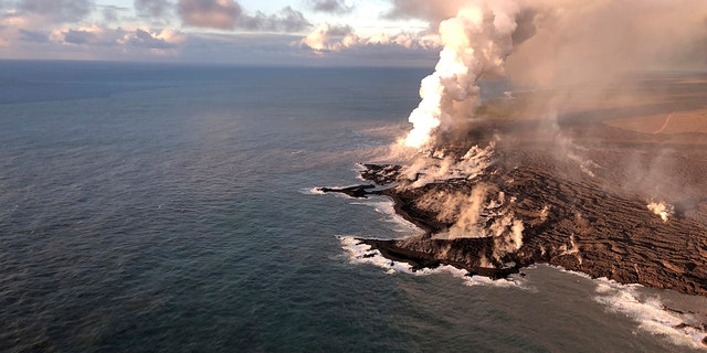 This photo provided by the U.S. Geological Survey shows where lava from Kilauea Volcano is entering the ocean and the resulting laze plume where lava is entering the sea at Kapoho on the island of Hawaii at dawn Wednesday, June 13, 2018.