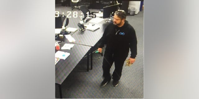 The purported surveillance camera image allegedly showing Afshin Pishevar approaching BamBrogan's desk with a noose coiled in his left hand (image from lawsuit).