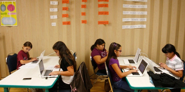 Students work at their computers in a classroom at the Cherokee Nation Immersion School in Tahlequah, Okla. Nearly two centuries after a Cherokee silversmith named Sequoyah developed a system of symbols for each syllable spoken by the Cherokee, the tribe's written language has become available on iPhone and iPods.