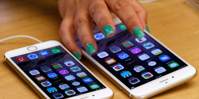 A woman touches an iPhone 6 Plus as it sits next to an iPhone 6 after they went on sale at the Apple store in Sydney.