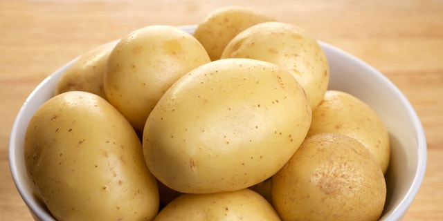 White potatoes in a porcelain bowl, on a wooden board.