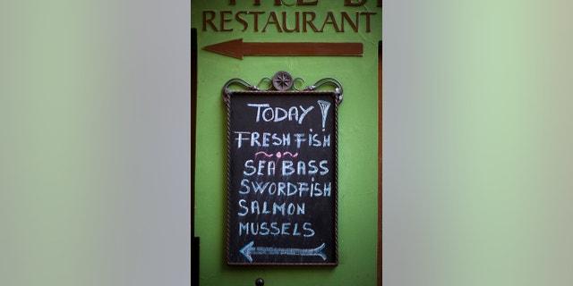 A chalkboard menu showing specials outside of a seafood restaurant in Prague, Czech Republic