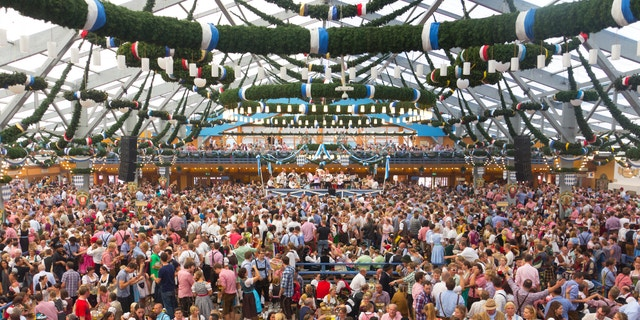 At the oktoberfest Munich. Hundreds or maybe thousands of poeple are inside one of the big beertents, sitting or standing on their benches, talking, drinking and having fun.  Many of them dressed in dirndls or leather pants.  In front is the band playing drinking songs.