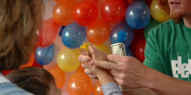 A little boy pays the money for a chance at a prize.