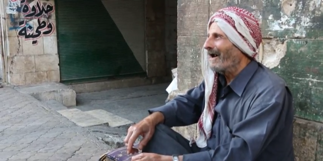 Old men sit in the streets inside Idlib, Syria clutching prayer beads and singing as they await the final offensive
