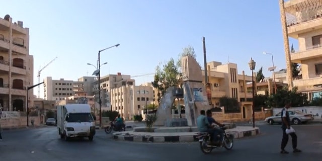 Men ride motorcycles calmly through the streets of Idlib, Syria