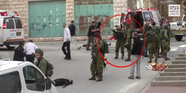Circled in red: An Israeli soldier seen holding a gun before firing at a Palestinian protester on the ground.