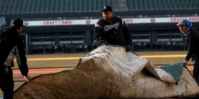 White Sox groundskeeper Nevest Coleman, center, helps Harry Smith Jr., left, and Jerry Powe with the tarp at Guaranteed Rate Field in Chicago.