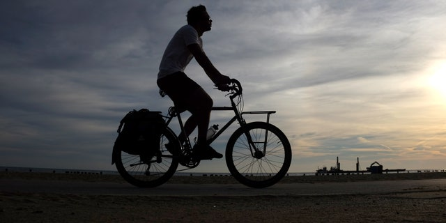 A commuter cruises on his bike on a trail along Lake Michigan, as he takes advantage of the mild early fall temperatures Thursday morning, Sept. 24, 2015, in Chicago. (AP Photo/Kiichiro Sato)