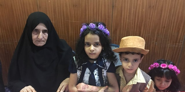 Amina (pictured) is the mother of a prominent Sana' journalist (his three children are pictured with Amina) who has been detained for more than three years. She explained that last time she tried to get close when visiting him, she was banned for seven months