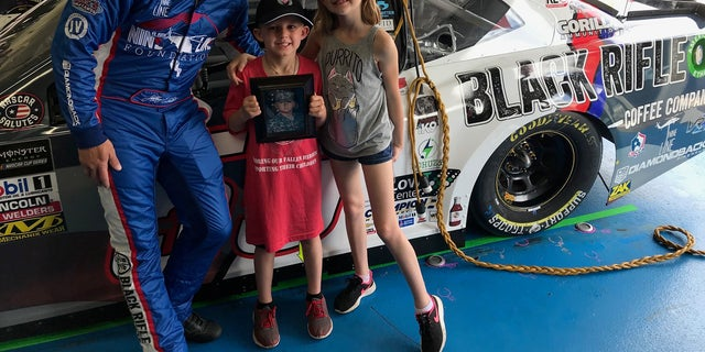 Jeffrey Earnhardy posing with Gino and Kayden Manis after revealing their father's name on his car.