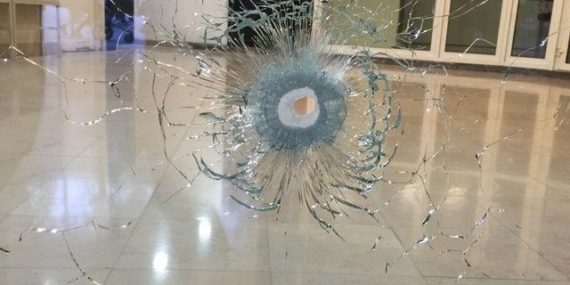 A window broken by a bullet.