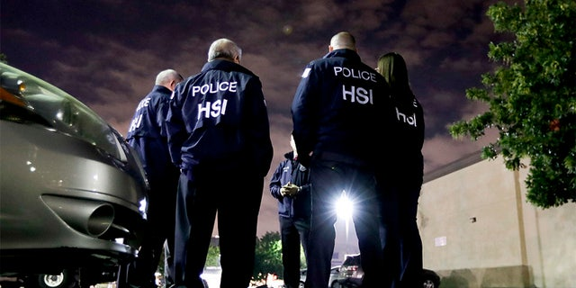 U.S. Immigration and Customs Enforcement agents gather before serving a employment audit notice at a 7-Eleven convenience store Wednesday, Jan. 10, 2018.