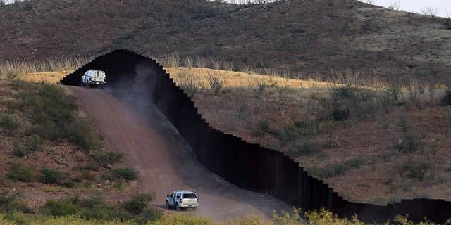 U.S. Border Patrol agents patrolling the border fence near Naco, Ariz.
