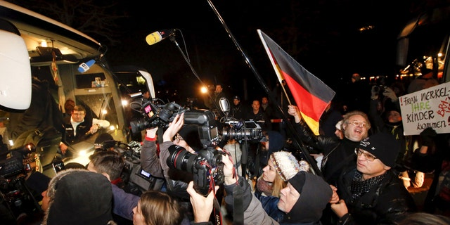 "Media and demonstrators waving a German national flag (R) and holding a banner wich reads ""Mrs. Merkel your children are coming! Bravo."" stand next to a bus with refugees from the Bavarian town of Landshut, after its arrival to the Chancellery building in Berlin, Germany, January 14, 2016."