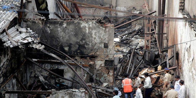 Indian fire officials inspect the burnt down shop in Mumbai, Monday, Dec. 18, 2017.