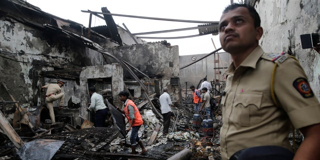 A police officer stands guard as fire officials clear the debris from a burnt down shop in Mumbai, Monday, Dec. 18, 2017.