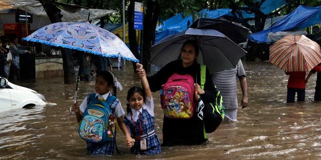 School children wade through a waterlogged street following heavy rains in Mumbia, India.