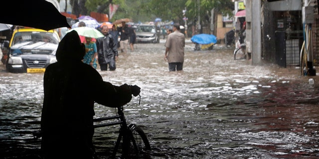 People move through waterlogged streets in Mumbia, India, following heavy rains.
