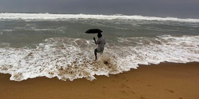 Oct. 11, 2013: An Indian man holds on to his umbrella as he fishes in high tide waves at Gopalpur beach, in Ganjam district, 136 miles away from the eastern Indian city of Bhubaneswar, India.
