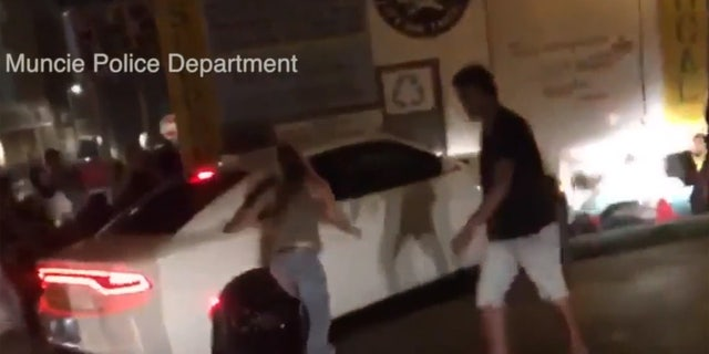 People can be seen getting knocked over by the car.