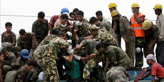 Indian rescue workers and security personnel bring out the body of a woman from a carriage at the site of a train crash near Sardiha, West Bengal state, about 150 kilometers (90 miles) west of Calcutta, India, early Friday, May 28, 2010. The overnight passenger train was derailed by an explosion then hit by another train early Friday as it traveled through a rebel stronghold of eastern India, officials said. A top government official said a number of people have been killed and scores injured. (AP Photo/Bikas Das)