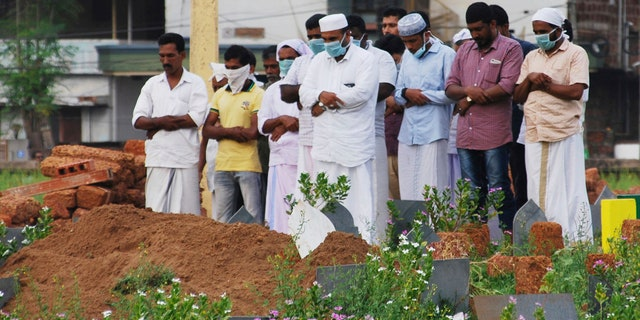 In this Thursday, May 24, 2018, photo, relatives and friends wear masks as a precautionary measure against the Nipah virus as they pray after the burial of Valachekutti Mosa's body, died of the same virus, in Kozhikode, in the southern Indian state of Kerala.