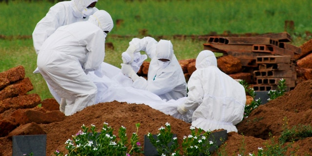 In this Thursday, May 24, 2018, photo, paramedics wear protective suits as a precautionary measure against the Nipah virus as they bury Valachekutti Mosa's body, died of the same virus, in Kozhikode, in the southern Indian state of Kerala.