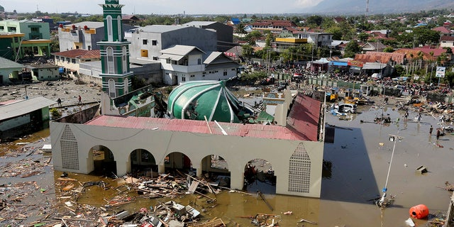 People survey the mosque damaged following earthquakes and tsunami in Palu, Central Sulawesi, Indonesia, Sept. 30, 2018.